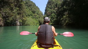 Man rowing kayak and looking back stock video footage