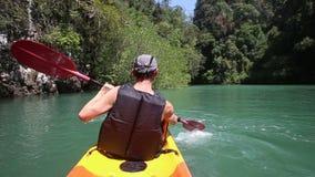 Man rowing kayak and waving paddle stock video