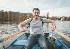 Man rowing on the river. Happy smiling man rowing on the river stock photos