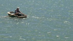 Man rowing a row boat at sea stock footage