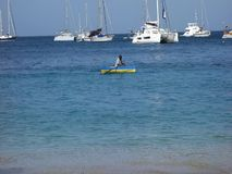 A man rowing a small boat in the windward islands stock video footage