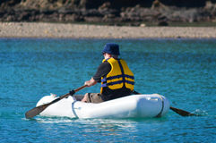 Man rows dinghy boat Stock Photos