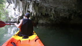 Man rows kayak in cliff cave stock video footage