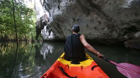 Man rows kayak in cliff cave stock footage