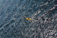 Man rows oar in kayak floats on sea Stock Photography