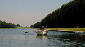 A man rows a paddle boat on a canal royalty free stock image