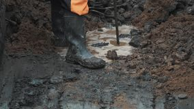 Man in rubber boots poking dirt puddle ground with piece of armature stock video footage