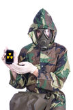 Man in a rubber gasmask. Man in a rubber hazmat holding a counter with radiation symbiol Stock Images