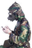 Man in a rubber gasmask. Man in a rubber hazmat holding a counter Royalty Free Stock Photography