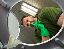 Man in rubber glove in the toilet Stock Images