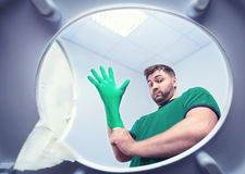 Man in rubber glove in the toilet Royalty Free Stock Images