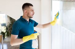 Man in rubber gloves cleaning window with rag Stock Photos