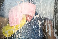 A man in rubber gloves washes a window. Homemade cleaning. Copy space. royalty free stock photos