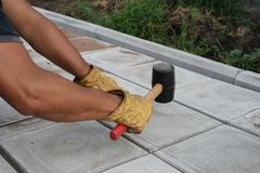 Man with Rubber Mallet Paving Royalty Free Stock Image