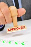 Man with a rubber stamp with the word approved Stock Photography