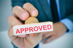 Man with a rubber stamp with the word approved Royalty Free Stock Photo