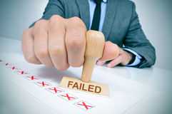 Man with a rubber stamp with the word failed. A young caucasian man at his office desk with a rubber stamp with the word failed stock photo
