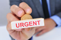 Man with a rubber stamp with the word urgent Stock Images