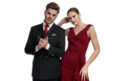 Man rubbing his hand while his girlfriend is posing. Confident you men dressed in a black suit rubbing his hand while his girlfriend wearing a red dress is stock image