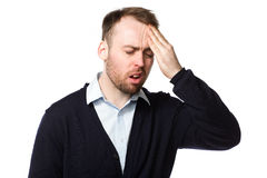 Man rubbing his throbbing forehead with his hand. As he grimaces and cries out in pain from his headache or migraine, upper body on white Stock Photography