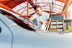 Man rubbing vehicle with car polish Stock Photography