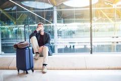 Man rubbningen, ledset, och ilsket på flygplatsen försenas hans flyg royaltyfri fotografi