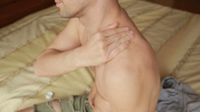 Man rubs cream shoulder. joint pain. cosmetic procedures. Man rubs cream shoulder. cosmetic procedures stock video footage