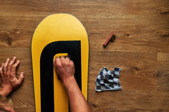 Man rubs snowboard sponge wax on  wooden floor Stock Photo