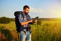 Man with rucksack watching something in his data tablet during a Royalty Free Stock Photos