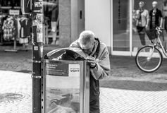 Man rummaging in a litter bin Stock Photography