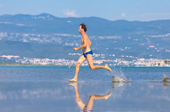 Man run across the beach Stock Photo