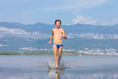 Man run across the beach Royalty Free Stock Photography