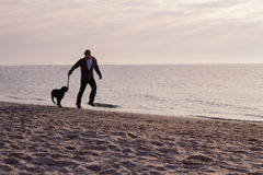 Man run with dog on the beach. Young caucasian male walking with dog on the morning beach, sunset on the sea or ocean and man with black labrador puppy Royalty Free Stock Image