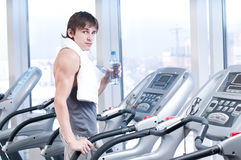 Man run on on a machine and drink water Royalty Free Stock Images