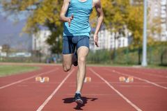 Man runner in blue shirt and shorts and sport shoes in steady position before run at start of race. Man runner in blue shirt and shorts and sport shoes in royalty free stock images