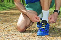 Man runner getting ready for jogging. Sport, active lifestyle concept. Fitness people using smart watch. Royalty Free Stock Photo