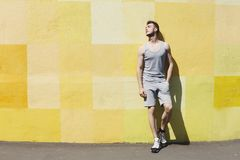 Man runner is having break, leaning at yellow wall. Man runner is having break after jogging in city, leaning at yellow painted wall, copy space stock images