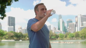 Man runner jogging in park. Fit male sport fitness running training. Drinking water from bottle. Handsome young man runner jogging in park. Fit male sport stock footage