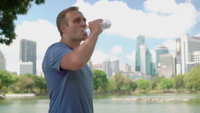 Man runner jogging in park. Fit male sport fitness running training. Drinking water from bottle. Handsome young man runner jogging in park. Fit male sport stock video footage