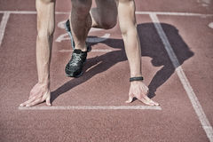 Man runner with muscular hands, legs start on running track Stock Images