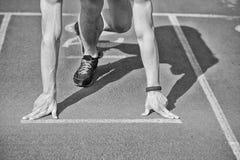 Man runner with muscular hands, legs start on running track Stock Image