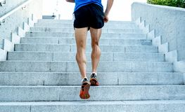 Close up of young man running up the stairs with running clothes royalty free stock image