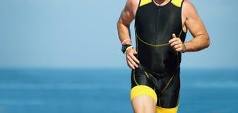 Man runner running on triathlon race. On sunny days at ocean royalty free stock photo