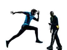 Man runner sprinter with coach  stopwatch Royalty Free Stock Images