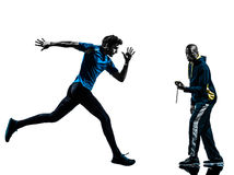 Man runner sprinter with coach  stopwatch silhouette. One caucasian men  running sprinting with coach stopwatch in silhouette studio isolated on white background Royalty Free Stock Photos