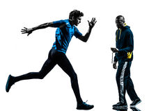 Man runner sprinter with coach  stopwatch silhouette Stock Image