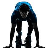 Man runner sprinter on starting blocks   silhouette. One caucasian man runner sprinter on starting blocks  in silhouette studio isolated on white background Stock Image