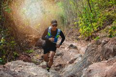 A man Runner of Trail . and athlete`s feet wearing sports shoes for trail running in the forest royalty free stock photo