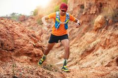 A man Runner of Trail . and athlete`s feet wearing sports shoes for trail running in the mountains stock photos
