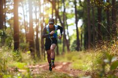 A man Runner of Trail . and athlete`s feet wearing sports shoes for trail running in the forest royalty free stock photography